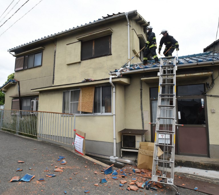 Firefighters check a house damaged by an earthquake in Ibaraki City north of Osaka prefecture