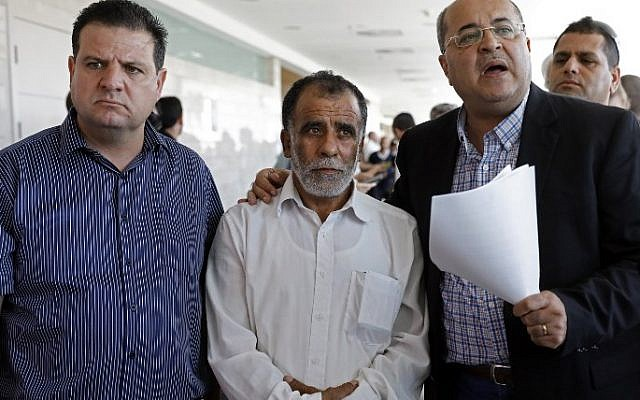 Hussein Dawabsha, center, grandfather of a Palestinian toddler who was burned to death with his parents at their family home, stands with Israeli parliament members Ayman Odeh, left, and Ahmad Tibi, during the trial of the two Jewish men suspected of carrying out the attack, on June 19, 2018 at a court in the town of Lod. AFP  / AHMAD GHARABLI)