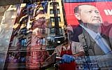 A worker slices meat as a reflection of a portrait of Turkish President Recep Tayyip Erdogan is seen in the window of a Turkish restaurant in Istanbul's Taksim Square on June 20, 2018. (AFP Photo/Bulent Kilic)