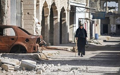 A woman walks with a cane past a destroyed car down a street in Al-Hirak in the eastern Daraa province countryside in southern Syria on June 21, 2018. (AFP PHOTO / Mohamad ABAZEED)