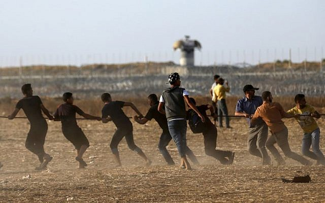 Illustrative. Palestinians pull on a metal cable as they try to take down a section of barbed wire on the border fence with Israel, east of Khan Younis in the southern Gaza Strip, on June 22, 2018. (AFP Photo/Said Khatib)