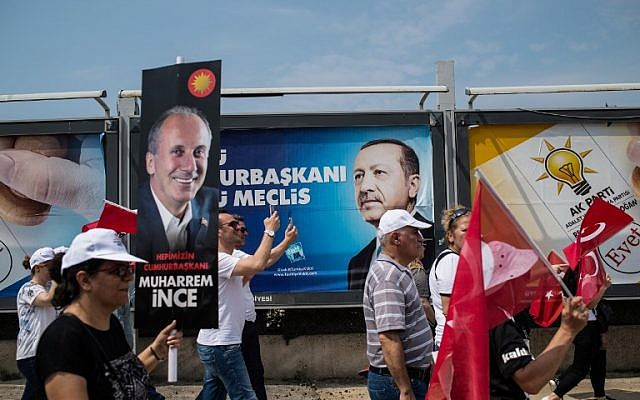 "A supporter of Muharrem Ince, Presidential candidate of Turkey's main opposition Republican People's Party holds a banner reading ""president of all of us"" and people wave flags, as an election poster of the President of Turkey Recep Tayyip Erdogan is seen behind, on June 23, 2018 in Istanbul. ( AFP/ Yasin AKGUL)"