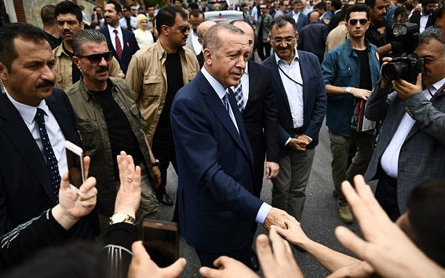 Turkey's president and leader of the Justice and Development Party (AKP), Recep Tayyip Erdogan (C), shakes hands with supporters, as he leaves the polling station after casting his vote.  (AFP PHOTO / ARIS MESSINIS)