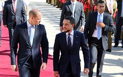 Prince William (L) is greeted at Amman's Marka military airport by Crown Prince Hussein bin Abdullah on June 24, 2018.  Prince William arrived in Jordan. (AFP Photo/Khalil Mazraawi)