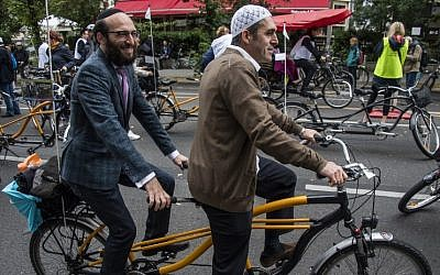 "Imam Osman Oers, front, and Rabbi Akiva Weingarten take the start on a tandem of the ""meet2respect"" bicycle demonstration in Berlin on June 24, 2018. (AFP Photo/John MacDougall)"