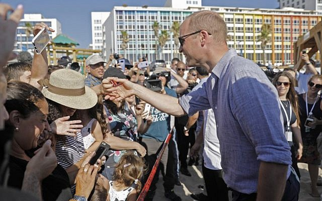 Britain's Prince William, right, reaches out to a person as reporters and beach-goers swarm around him, during a visit to a beach in the coastal Mediterranean city of Tel Aviv, June 26, 2018. (Menahem KAHANA/AFP)