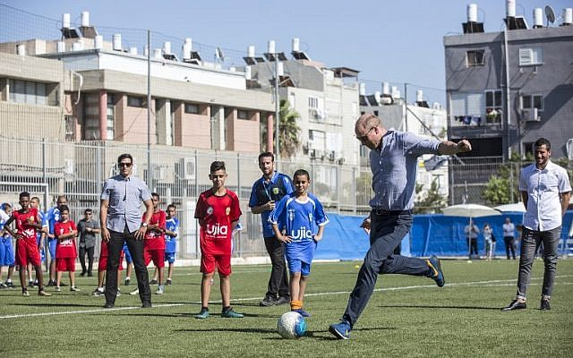 Britain's Prince William, center-right, prepares to kick a ball as he meets with Jewish and Arab children at the Neve Golan Stadium in Jaffa, June 26, 2018. (Heidi Levine/AFP)