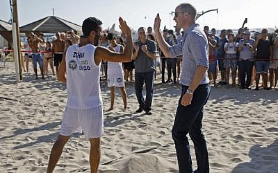 Britain's Prince William (R) high-fives a beach volleyball player during a visit with the mayor of Tel Aviv in the coastal city on June 26, 2018 (AFP PHOTO / POOL / MENAHEM KAHANA)
