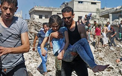 A man carries a child rescued from rubble after Syrian regime and Russian air strikes in the rebel-held town of Nawa, about 30 kilometers north of Daraa in southern Syria, June 26, 2018. (Ahmad al-Msalam/AFP)