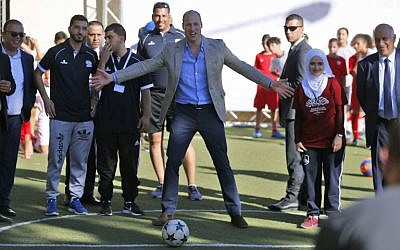 Britain's Prince William (C) prepares to shoot a soccer ball during his meeting with young Palestinian soccer players in the West Bank city of Ramallah on June 27, 2018. (AFP Photo/Abbas Momani)