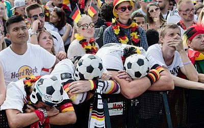 Supporters of the German national football team react as they attend a public viewing event at the Fanmeile in Berlin to watch the Russia 2018 World Cup Group F football match between South Korea and Germany on June 27, 2018. (AFP PHOTO / dpa / Bernd von Jutrczenka)