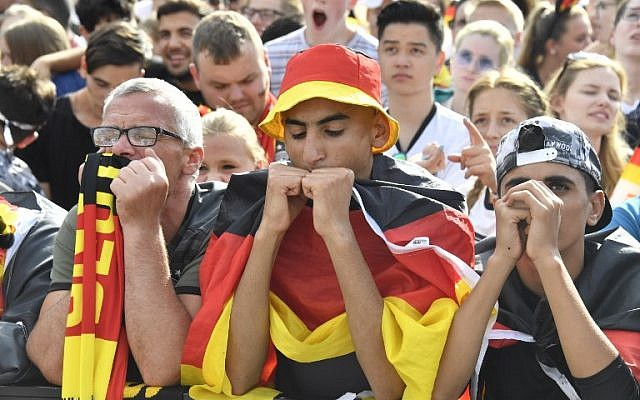 Supporters of the German national football team react as they attend a public viewing event at the Fanmeile in Berlin to watch the Russia 2018 World Cup Group F football match between South Korea and Germany on June 27, 2018. (AFP PHOTO / John MACDOUGALL)