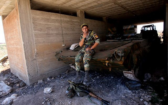 A Syrian government forces' soldier smokes a cigarette on an armored vehicle during a government guided tour in the village of al-Sourah, province of Daraa, on June 29, 2018. (AFP PHOTO / Youssef KARWASHAN)