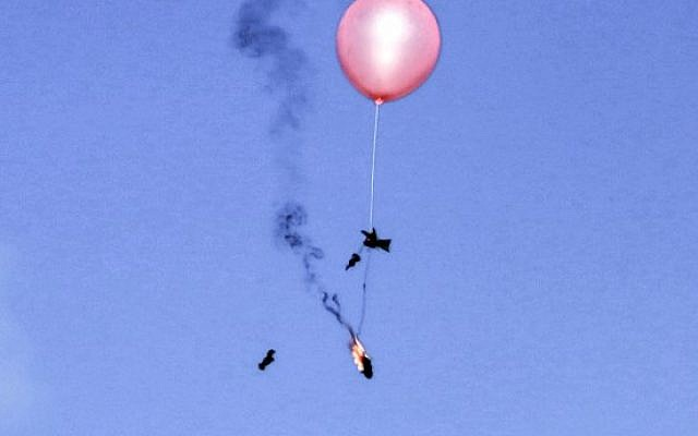A balloon loaded with incendiary material is flown towards Israel by Palestinians east of Gaza City