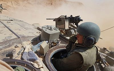 A female soldier operates a tank in the Negev desert in an undated photograph. (Israel Defense Forces)