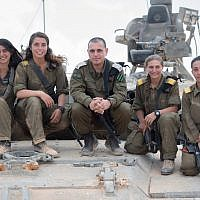 Head of the IDF Armored Corps Brig. Gen. Guy Hasson, center, poses on a tank with the army's first female tank commanders, who are graduating their course on June 28, 2018. (Israel Defense Forces)
