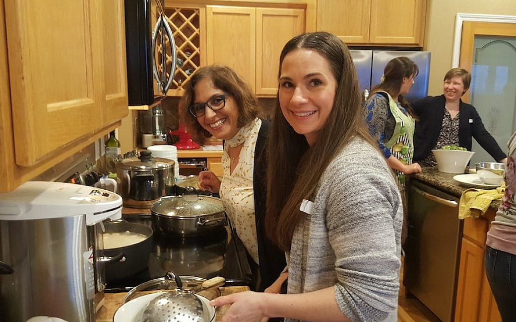 Efi Asaf, left, and Rachel Brown cooking matzah balls at a Mevashlim B'Ivrit class in Boise, Idaho. (Courtesy of Asaf/via JTA)
