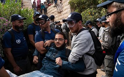 Police remove a demonstrator from a home in Netiv Ha'avot, June 12, 2018. (Luke Tress/Times of Israel)