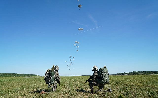Israeli soldiers take position as other paratroopers land behind them during the US-led Swift Response exercise in Europe in June 2018. (Israel Defense Forces)