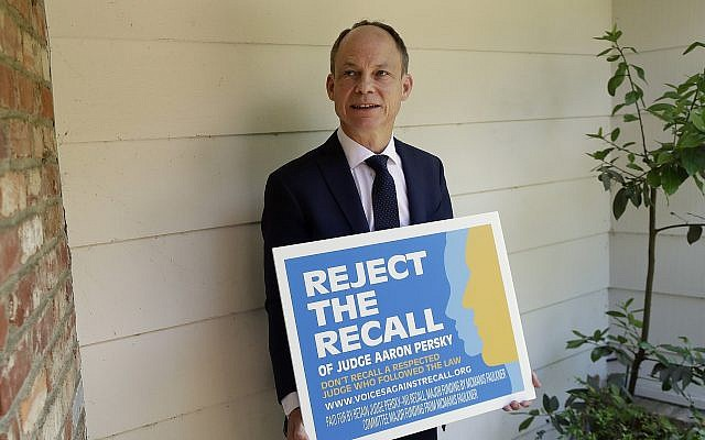 Judge Aaron Persky poses for a photo with a sign opposing his recall in Los Altos Hills, California, May 15, 2018. (Jeff Chiu/AP)