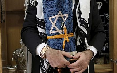In this May 30, 2018 photo, Rabbi Arie Zeev Raskin, the leader of Cyprus' 3,500-strong Jewish community, holds a rare 200 year-old Torah scroll that comes from Germany at a Synagogue inside Cyprus' Jewish Community Center in the town of Larnaca. (AP Photo/Petros Karadjias)