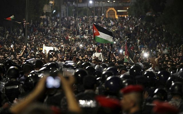 Jordanian protesters shout slogans and raise a national flag during a demonstration outside the Prime Minister's office in the capital Amman early Monday, June 4, 2018. (AP/Raad Adayleh)