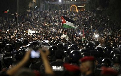 Jordanian protesters shout slogans and raise a national flag during a demonstration outside the Prime Minister's office in the capital Amman early June 4, 2018. (AP Photo/Raad Adayleh)