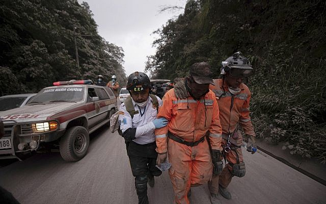 Firefighters leave the evacuation area near Volcan de Fuego, or Volcano of Fire, in El Rodeo, Guatemala, June 3, 2018. (AP/Santiago Billy)