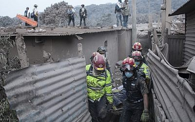 Firefighters remove a body recovered near the Volcan de Fuego in Escuintla, Guatemala, Monday, June 4, 2018.. (AP Photo/Oliver de Ros)