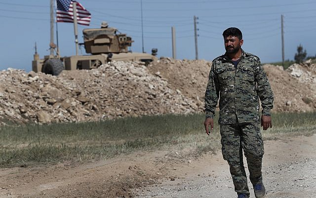 In this April 4, 2018 file photo, a US-backed Syrian Manbij Military Council soldier passes a US position near the tense front line with Turkish-backed fighters, in Manbij, north Syria. (AP Photo/Hussein Malla, File)
