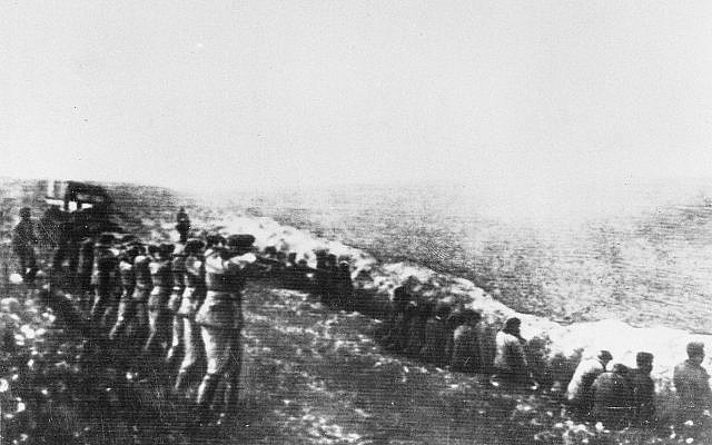Photo taken from the body of a dead German officer killed in Russia, showing a Nazi firing squad shooting Jews in the back as they sit beside their own mass grave, in Babi Yar, Kiev, 1942. (AP Photo, file)