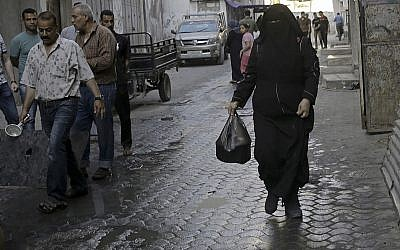 In this May 31, 2018, photo, Samia Hassan, walks with free porridge distributed by Walid al-Hattab, who cooks the free meals as Ramadan charity, in Gaza City. (AP Photo/Adel Hana)