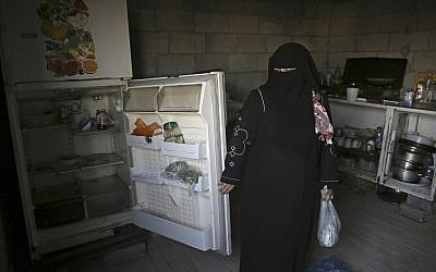 Samia Hassan shows her family's nearly empty refrigerator in Gaza City, May 31, 2018. (AP Photo/Adel Hana)