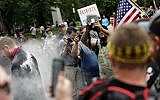 In this June 3, 2018, file photo, photographers capture dueling US demonstrations between antifascists known as antifa and a right wing group called Patriot Prayer in downtown Portland, Oregon. (Mark Graves/The Oregonian via AP, file)