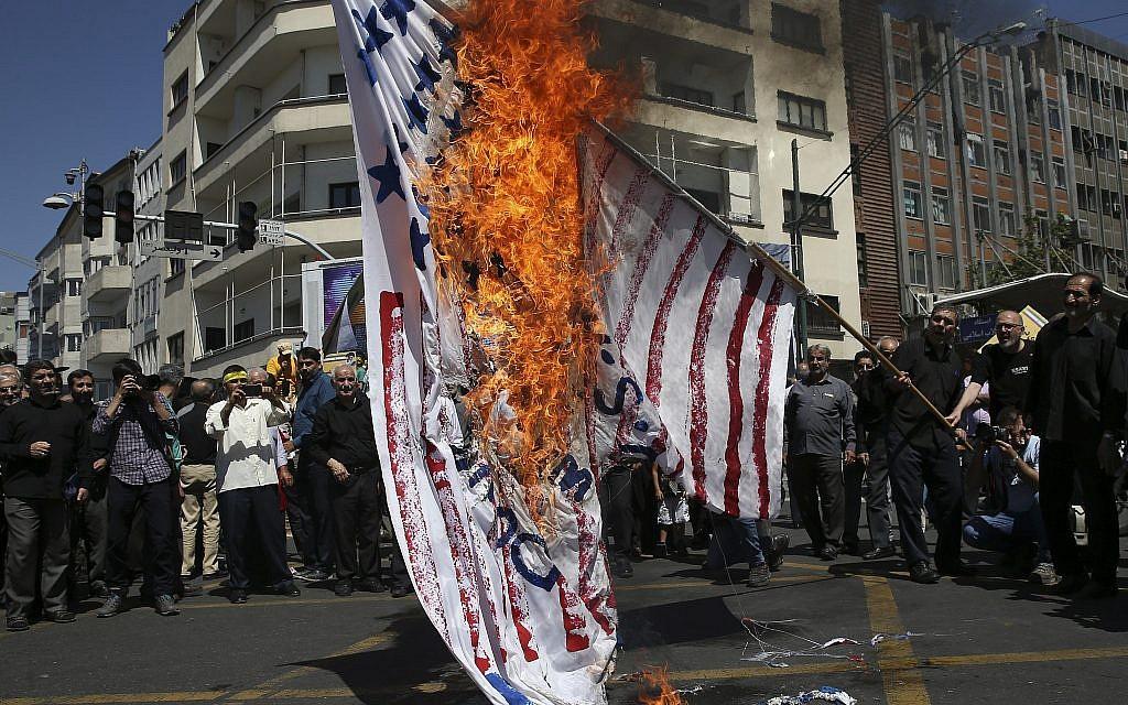 Iranian protesters burn a representation of the US flag in their annual anti-Israeli Al-Quds, Jerusalem, Day rally in Tehran, Iran, June 8, 2018. (Vahid Salemi/AP)