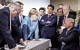 German Chancellor Angela Merkel, center, speaks with US President Donald Trump, seated at right, during the G7 Leaders Summit in La Malbaie, Quebec, Canada, June 9, 2018. (Jesco Denzel/German Federal Government via AP)