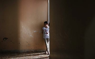 Under the watchful eye of an instructor, left, Batool Lababidi, a Syrian orphan from Aleppo, stands outside her room at an orphanage in Jarablus, northern Syria, May 30, 2018. (Lefteris Pitarakis/AP)