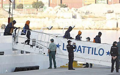Migrants descend the Italian coast guard vessel Dattilo upon arrival at the eastern port of Valencia, Spain, Sunday, June 17, 2018. (AP/Alberto Saiz)