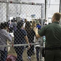 In this photo a US Border Patrol agent watches as people who've been taken into custody related to cases of illegal entry into the United States, stand in line at a facility in McAllen, Texas, Sunday, June 17, 2018. (US Customs and Border Protection's Rio Grande Valley Sector via AP)