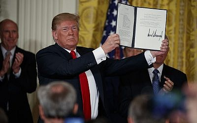 US President Donald Trump shows off a 'Space Policy Directive' after signing it during a meeting of the National Space Council at the White House on June 18, 2018. (AP Photo/Evan Vucci)