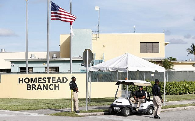 Security guards stand outside a former Job Corps site that now houses child immigrants, June 18, 2018. (AP Photo/Wilfredo Lee)