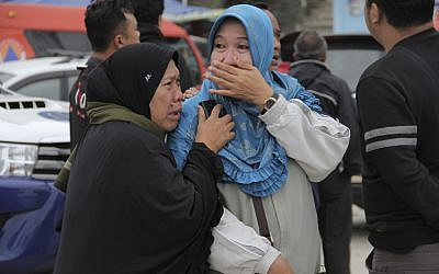 Relatives weep at Tigaras port after learning that their family members are among the passengers of a ferry which sank on Monday, in Simalungun, North Sumatera, Indonesia, Tuesday, June 19, 2018. (AP Photo/ Lazuardy Fahmi)