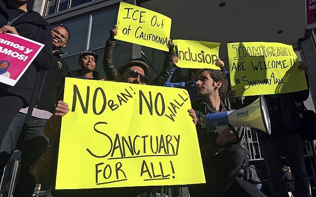 In this April 14, 2017, file photo, protesters hold up signs outside a courthouse where a federal judge was to hear arguments in the first lawsuit challenging President Donald Trump's executive order to withhold funding from communities that limit cooperation with immigration authorities in San Francisco (AP Photo/Haven Daley, File)