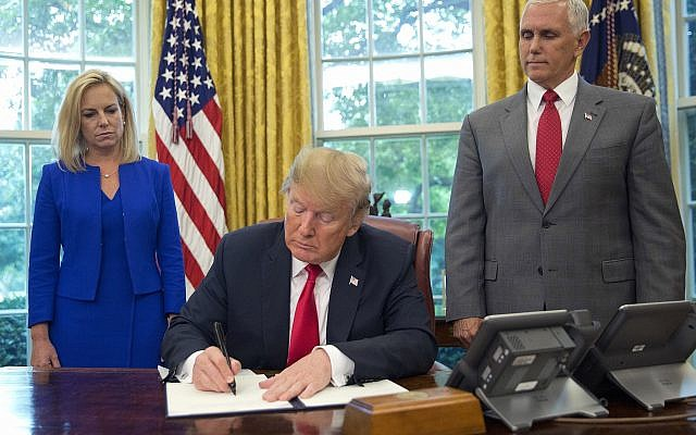 US President Donald Trump signs an executive order to keep families together at the border, but says that the 'zero-tolerance' prosecution policy will continue, during an event in the Oval Office of the White House, on June 20, 2018. (AP Photo/Pablo Martinez Monsivais)