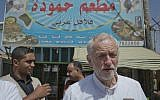 "United Kingdom's Labour party leader Jeremy Corbyn walks in the main market road during his visit to the Zaatari Syrian Refugee Camp, in Mafraq, Jordan, Friday, June 22, 2018. Arabic in background reads ""Hamoudah restaurant, Arabic Falafel."" (AP Photo/Nasser Nasser)"