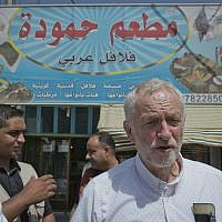UK Labour Party leader Jeremy Corbyn walks in the main market road during his visit to the Zaatari Syrian Refugee Camp, in Mafraq, Jordan, Friday, June 22, 2018. Arabic in background reads 'Hamoudah restaurant, Arabic Falafel.' (AP Photo/Nasser Nasser)