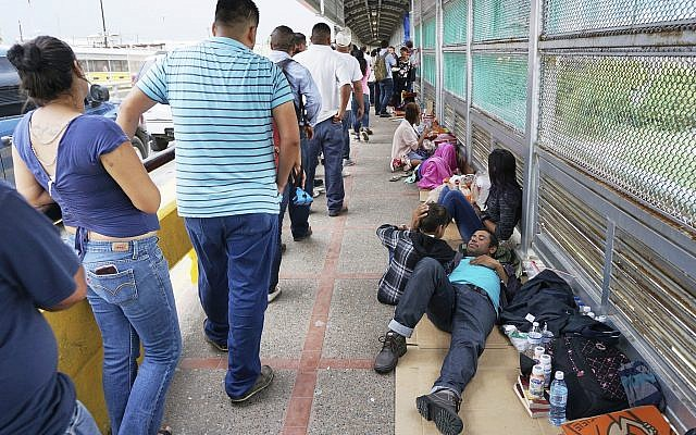 Migrant families rest from their travels to Matamoros, Mexico, along Gateway International Bridge which connects to Brownsville, Texas, as they seek asylum in the United States. (Miguel Roberts/The Brownsville Herald via AP)