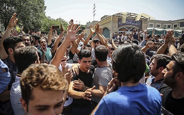 A group of protesters chant slogans at the main gate of old Grand Bazaar in Tehran, Iran, June 25, 2018. (Iranian Labor News Agency via AP)