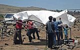 This June 22, 2018 photo provided by Nabaa Media, a Syrian opposition media outlet, shows people who fled from Daraa setting up a tent in the village of Bregia, near the Syria-Israel border, southern Syria. (Nabaa Media, via AP)