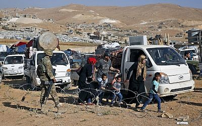 A Lebanese soldier stands guard as Syrian refugees gather in their vehicles getting ready to cross into Syria from the eastern Lebanese border town of Arsal, Lebanon, on June 28, 2018. (AP Photo/Bilal Hussein)